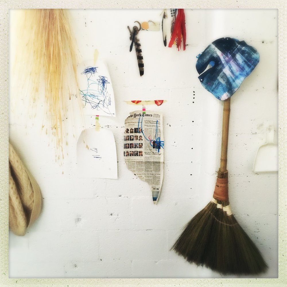 studio snap, a wall, from left the arm of a sweater from a loved and now-elsewhere friend, the Usual broomstraws, Eleni's breakfast efforts, Eleni's censorship of Trump appointees, a beloved broom and a far less beloved dust pan