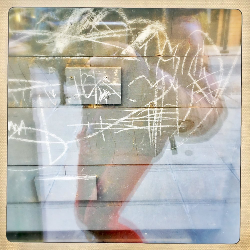 in a restaurant window. Possibly where a very small hoodlum crept behind a dinner booth and made haste with chalk from the outdoor sandwich board. Not incidental, but certainly pure.