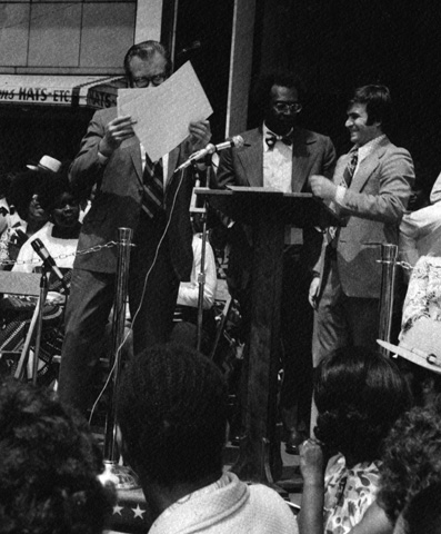 Dr. Eugene Callendar, Urban League President (center), with Paul Austin and Hussein at podium