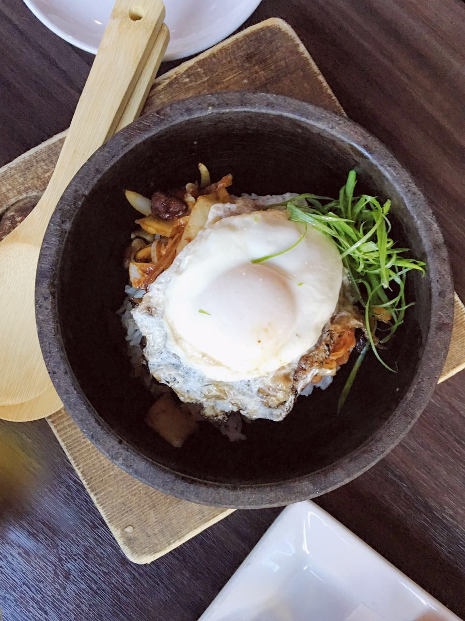 Spicy Chashu Stone Bowl - Sunny side up egg on top of tender bbq pork slices and a bed of rice, garnished with kimchi and green chives.