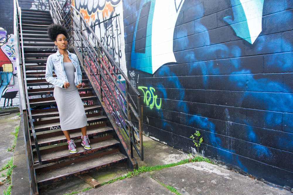 Dresses to wear with sneakers? Yes, it's possible! Got my shoes bedazzled and a basic dress to complete this sneaker outfit. You'll also find a couple of dresses in this post to help you develop your own sneaker style.  Photo taken in Houston, in front of a graffiti mural. Rocking some custom made nikes, denim jean jacket, hoop earrings, and a gray bodycon dress from Forever 21.