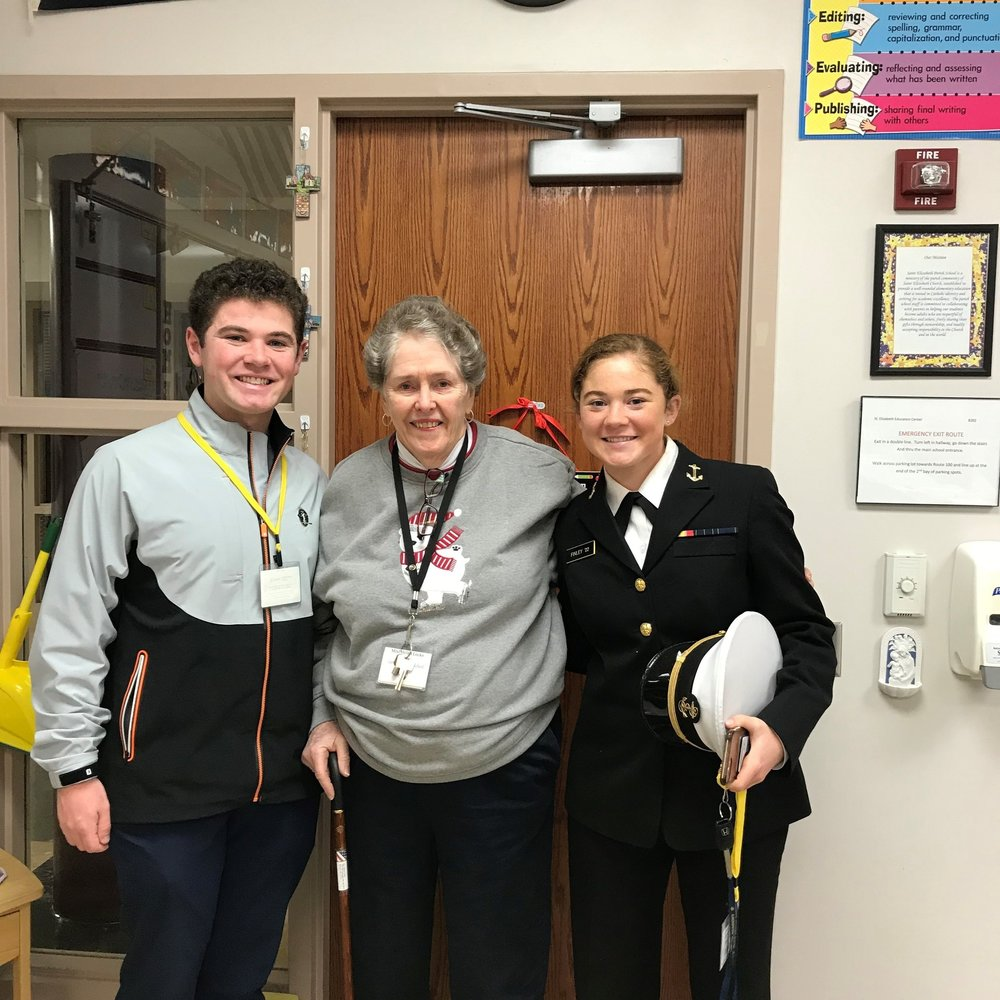 Two of our alumni paid a visit to the school today. Vince Finley (Class of 2012, left) currently studies at Loyola University & sister Erin Finley (Class of 2014) currently studies at the U.S. Naval Academy. They are pictured with teacher, Mrs. Helen Locke. (Photo: Mrs. Jennifer Grygo)