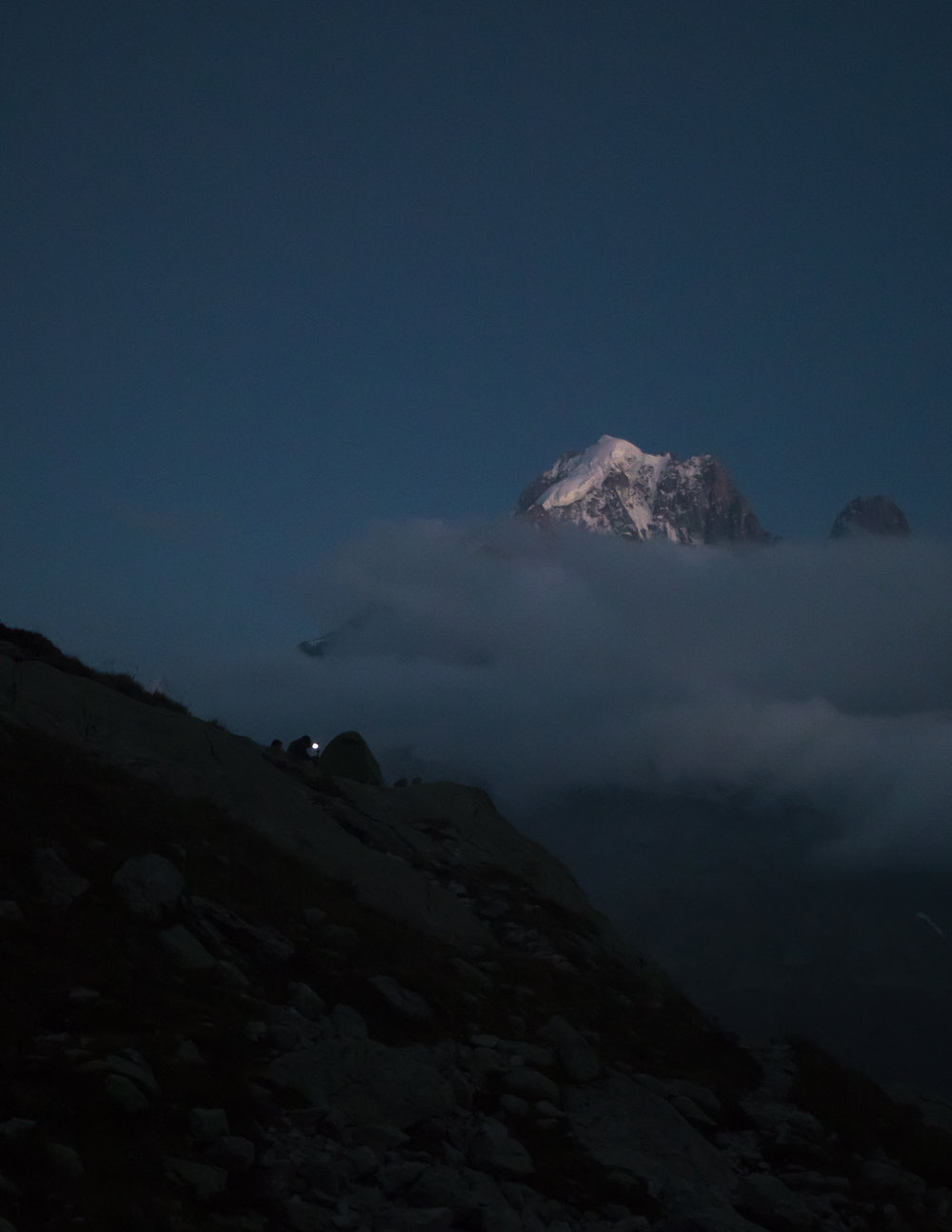 Cooking under headlamp light during an impressive blue hour in the Chamonix valley.