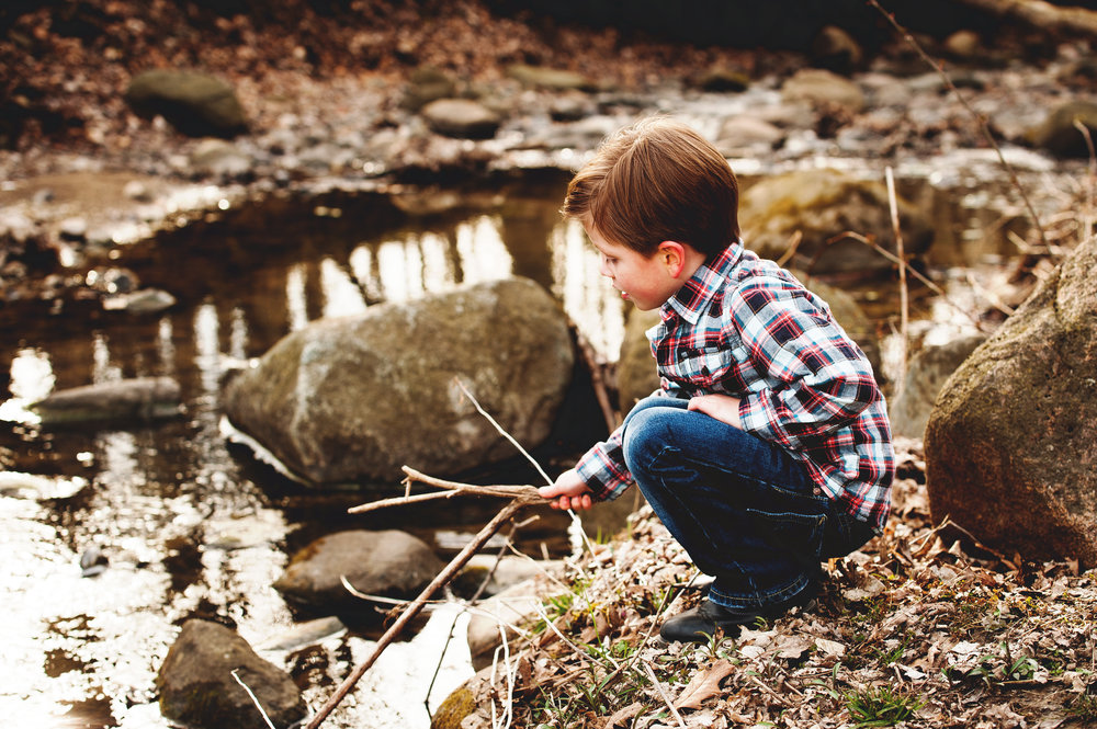 A little boy can't overlook a creek.