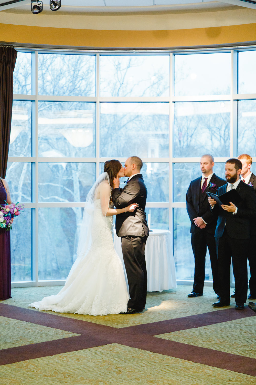 ceremony-first-kiss-a-ohio-lighting-ocf-columbus-wedding-couple-bridal-creekside-conference-indoor-roxanna-sue-photos-ohio-photography-1.jpg