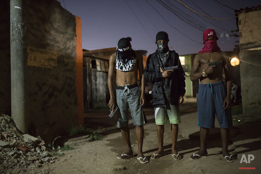 In this July 11, 2016 photo, young drug traffickers pose for photos holding their guns at a slum in Rio de Janeiro, Brazil. Teenage boys openly tote guns as they run in flip-flops through a maze of alleys. When Associated Press journalists visit areas with authorization from the gangs, the ones who agree to be photographed cover their faces so they can't be identified. (AP Photo/Felipe Dana)