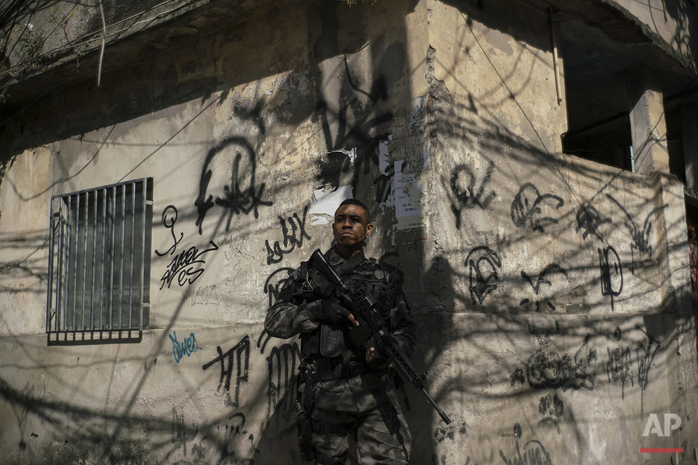 "In this June 29, 2016 photo, a police officer takes position during an operation against drug traffickers at the ""pacified"" Jacarezinho slum in Rio de Janeiro, Brazil. The number of people killed by police has spiked in the past two years after dropping significantly the previous six. Overall murders are also on the rise in the first half of 2016, just as officials wanted to use the Aug. 5-21 Olympic Games to showcase the city as a tourist destination. (AP Photo/Felipe Dana)"