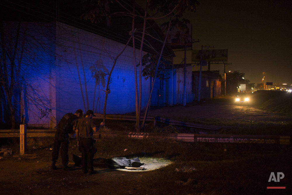 In this July 15, 2016 photo, police officers use a flashlight to inspect the crime scene where the body of an alleged thief was found on a roadside in Nova Iguacu, greater Rio de Janeiro, Brazil. Gruesome scenes of death and impunity play out daily in Rio's hundreds of shantytowns, known as favelas. (AP Photo/Felipe Dana)