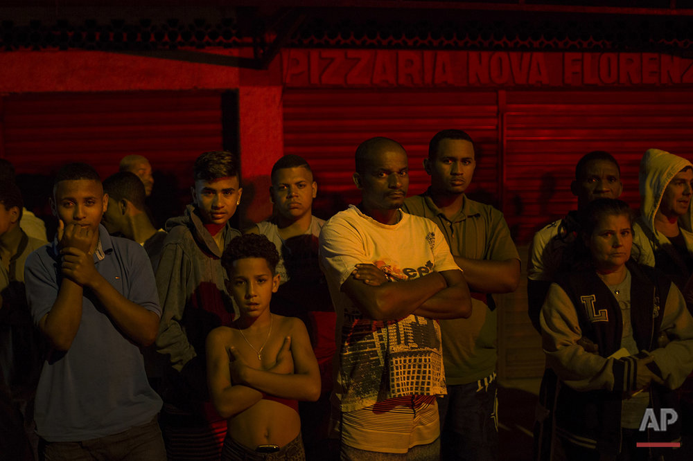 In this July 15, 2016 photo, residents watch as police work the crime scene where a man was murdered in Mage, greater Rio de Janeiro, Brazil. Scenes of impunity and violence play out daily in many of Rio's hundreds of slums, known here as favelas, and other outlying areas. The vast majority of killings are the result of heavily armed gangs who frequently shoot it out in turf wars. (AP Photo/Felipe Dana)