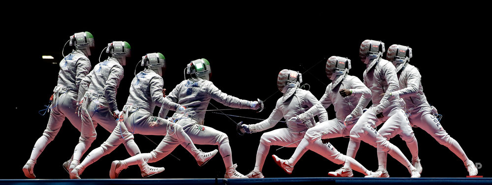 In a photo taken using multiple exposure, Iran's Mojtaba Abedini, left, and United State's Daryl Homer compete in a men's individual sabre semifinal at the 2016 Summer Olympics in Rio de Janeiro, Brazil, Wednesday, Aug. 10, 2016. (AP Photo/Charlie Riedel)
