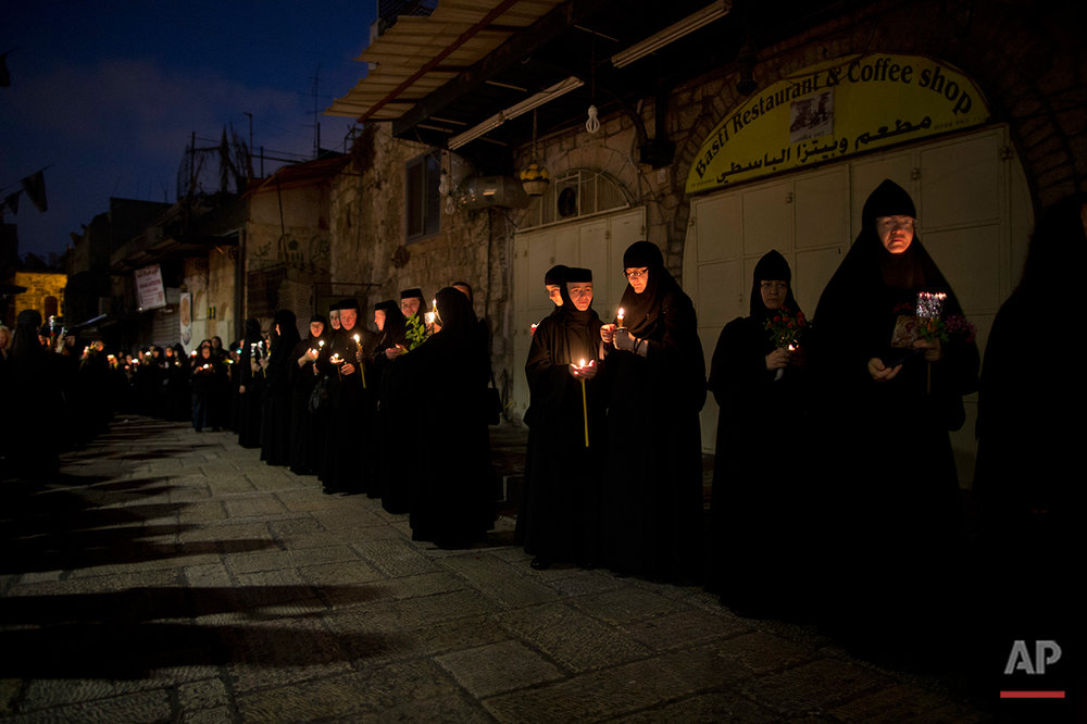 Orthodox nuns hold candles and flowers as they walk in a procession to bring the icon of the Virgin Mary to the tomb where it is believed she is buried, through Jerusalem's Old City, early Thursday, Aug. 25, 2016. Every year before the Feast of the Assumption, the icon is brought from the Church of the Holy Sepulchre to the tomb of the Virgin Mary to honor her Assumption. (AP Photo/Oded Balilty)