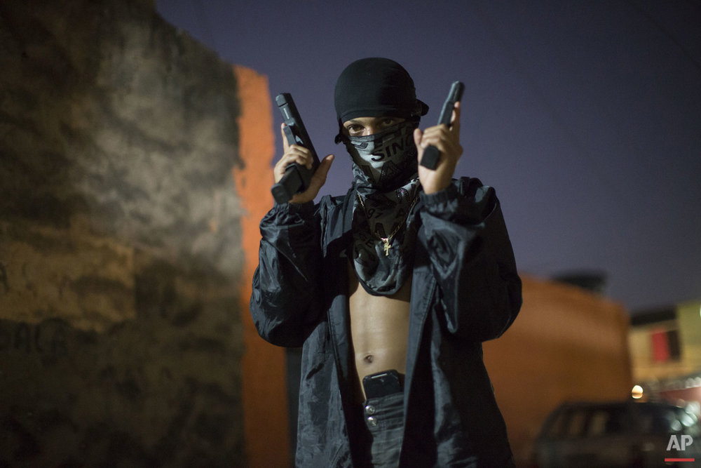 In this July 11, 2016 photo, a young, masked drug trafficker poses for photos holding his guns at a slum in Rio de Janeiro, Brazil.  (AP Photo/Felipe Dana)