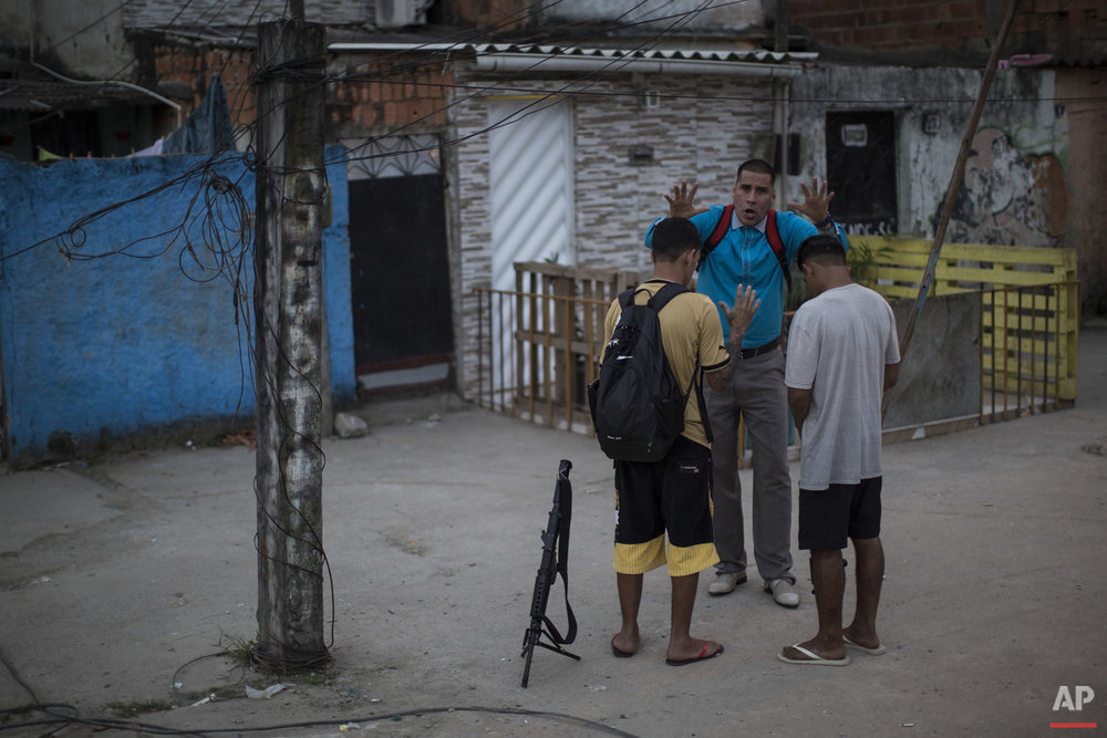 In this July 16, 2016 photo, pastor Nilton blesses two young drug traffickers at a slum in Rio de Janeiro, Brazil. Many of the young drug traffickers have an immense respect for the pastor, a former drug trafficker. It's not uncommon to see young men set their weapons down, but only long enough to receive his blessing.(AP Photo/Felipe Dana)