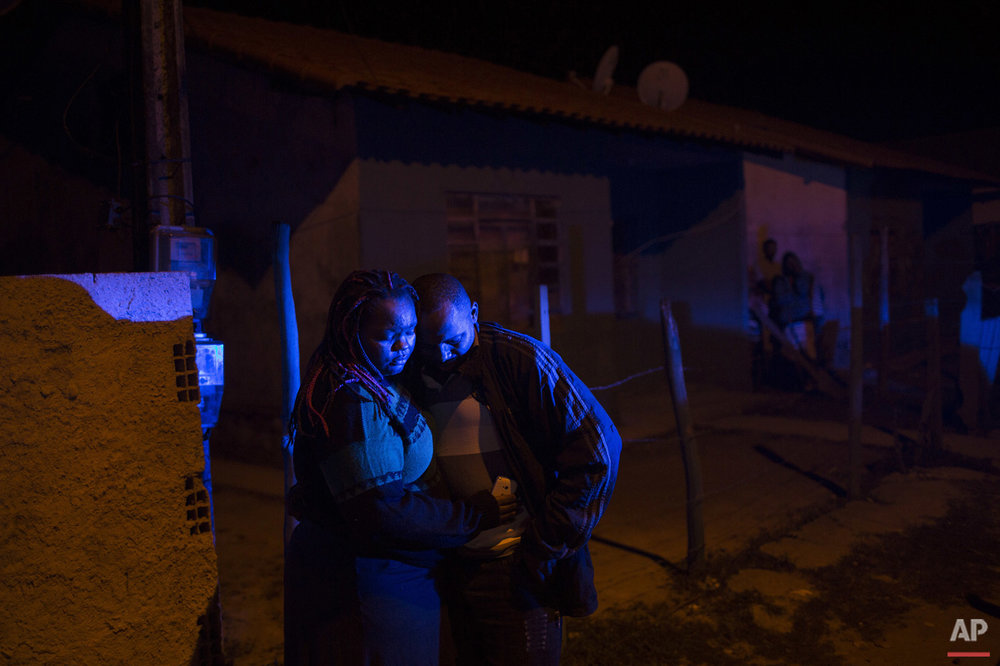 In this July 13, 2016 photo, an eyewitness stands with a woman outside a bar where a pre-candidate for local council was shot dead in Mage, in greater Rio de Janeiro, Brazil. According to local news reports the 49-year-old woman was shot by four gunmen while in a bar with a friend and her partner. The woman is the 11th politician murdered in the greater Rio area since November, and police have not been able to determine the motives for the killings. (AP Photo/Felipe Dana)