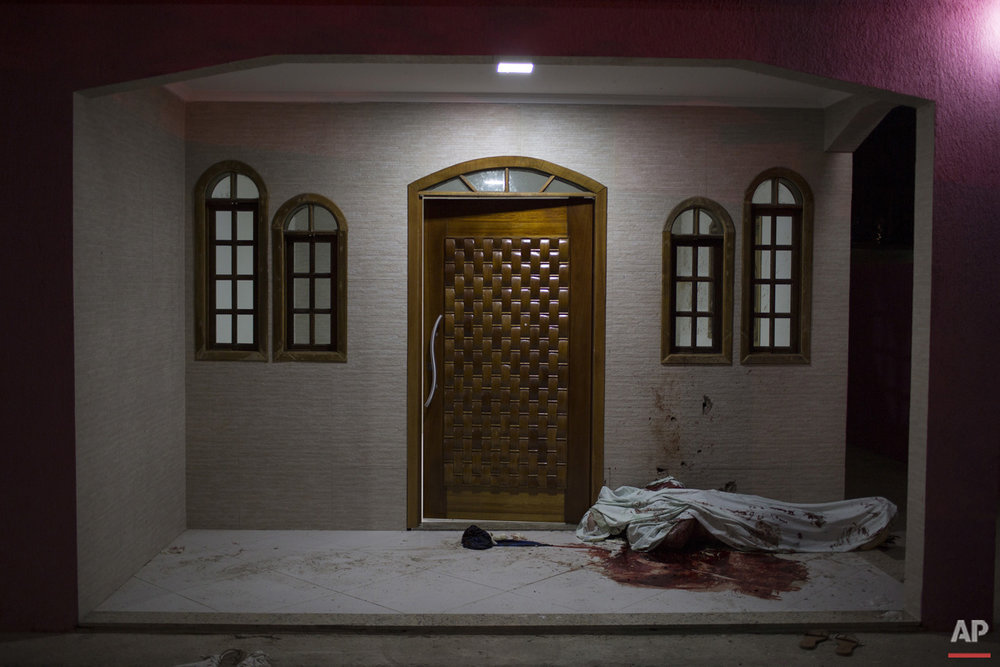 This July 13, 2016 photo shows a crime scene at the entrance of a home in Nova Iguacu, greater Rio de Janeiro, Brazil. The man who lived there with his family was removed by gunmen and killed on the spot. Police believe the killing was a gang hit related to a change of leadership in the area.  (AP Photo/Felipe Dana)