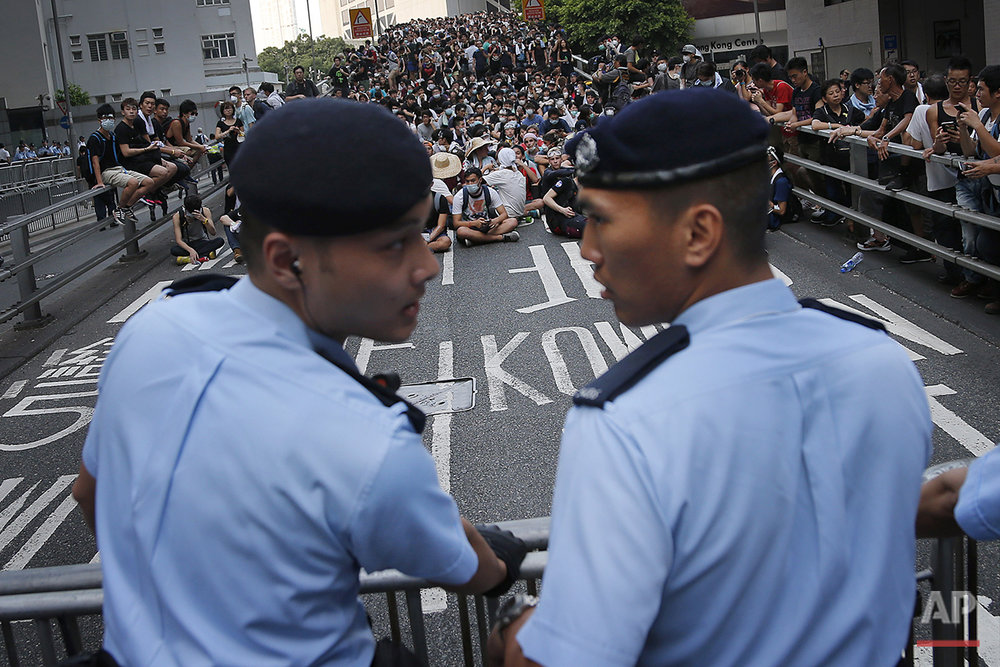 Pro-democracy protesters sit on a road as they face-off with local police, Monday, Sept. 29, 2014 in Hong Kong. (AP Photo/Wong Maye-E)