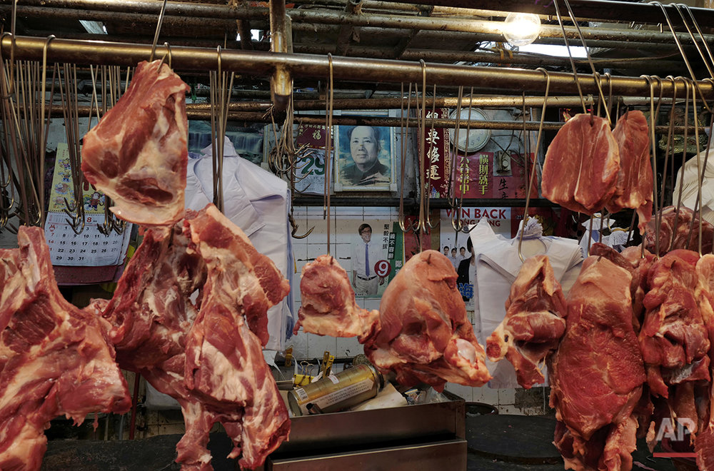 In this Tuesday, Aug. 30, 2016 photo, an election campaign poster for pro-democracy candidate Andrew Cheng is seen under a portrait of Chinese leader Mao Zedong at a butcher's stall in a Hong Kong market. Hong Kongers head to the polls Sunday, Sept. 4, 2016 to choose candidates for the semiautonomous city's legislature, in the first major election since 2014's pro-democracy street protests. That movement drew world attention to the former British colony's struggle over stunted democratic development under Chinese rule and paved the way for a burgeoning independence movement that's complicating the upcoming vote. (AP Photo/Vincent Yu)
