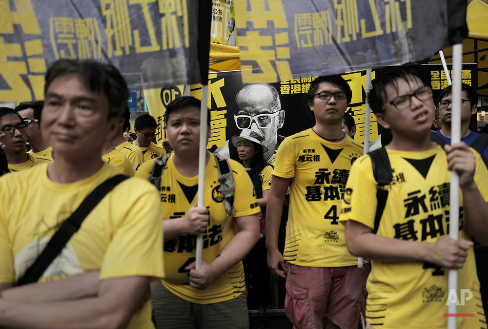 In this Aug. 27, 2016 photo, supporters of radical localist group Civic Passion hold banners in front of a photo of candidate Wong Yeung-tat at a pre-election rally in Hong Kong. (AP Photo/Vincent Yu)