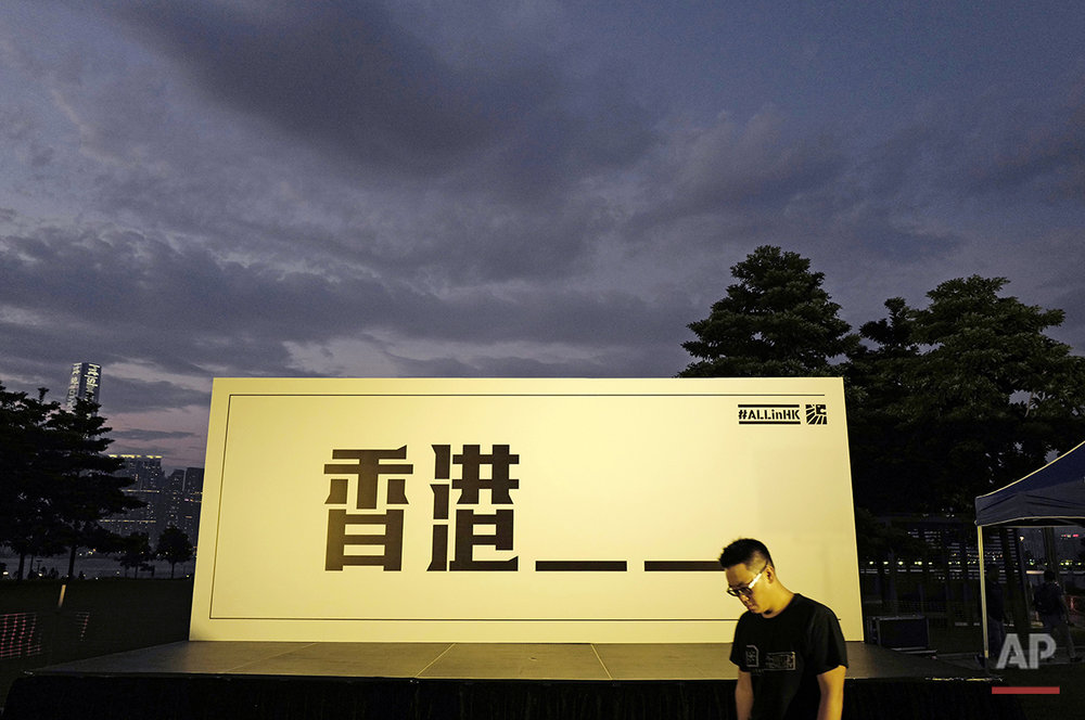 "In this Aug. 28, 2016, photo, a supporter walks past a backdrop for a pre-election rally in Hong Kong. Characters reads ""Hong Kong"" leaving out the word ""independence,"" a reference to the government's attempt to disqualify candidates promoting independence for the Chinese city. (AP Photo/Vincent Yu)"