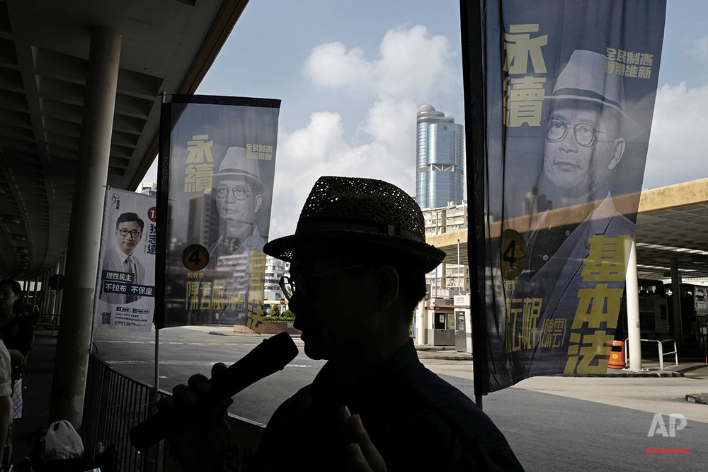 "In this Aug. 25, 2016 photo, Horace Chin, a candidate in Hong Kong's upcoming legislative elections who's known as the ""godfather of localism,"" is flanked by his campaign banners in Hong Kong. Hong Kongers head to the polls Sunday, Sept. 4, 2016 to choose candidates for the semiautonomous city's legislature, in the first major election since 2014's pro-democracy street protests. That movement drew world attention to the former British colony's struggle over stunted democratic development under Chinese rule and paved the way for a burgeoning independence movement that's complicating the upcoming vote. (AP Photo/Vincent Yu)"