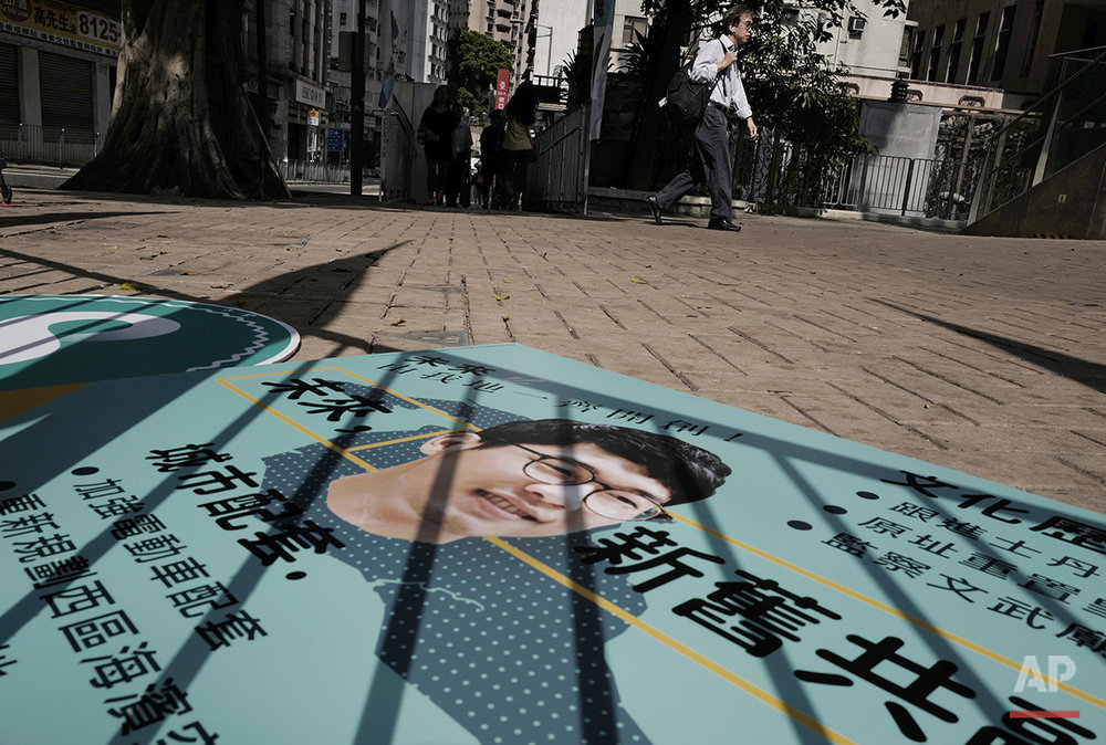 "In this Aug. 26, 2016 photo, shadows fall over campaign signs for rookie Hong Kong election candidate Nathan Law of the Demosisto party in Hong Kong which proposes a referendum on ""self determination"" for the Chinese city's future. (AP Photo/Vincent Yu)"
