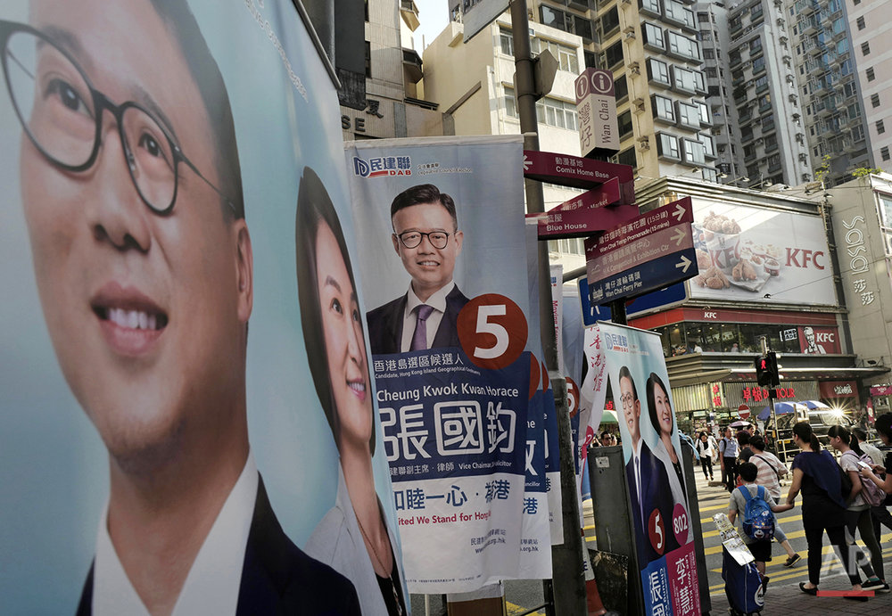 In this Aug. 25, 2016 photo, people walk past election banners on a Hong Kong street for pro-Beijing candidate Horace Cheung. Hong Kongers head to the polls Sunday, Sept. 4, 2016 to choose candidates for the semiautonomous city's legislature, in the first major election since 2014's pro-democracy street protests. That movement drew world attention to the former British colony's struggle over stunted democratic development under Chinese rule and paved the way for a burgeoning independence movement that's complicating the upcoming vote. (AP Photo/Vincent Yu)