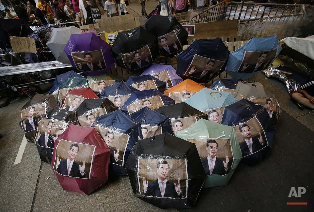 "Iconic umbrellas used in the pro-democracy protests dubbed ""The Umbrella Revolution"" are used to display portraits of Hong Kong's embattled leader Leung Chun-ying in an occupied area in the Mong Kok district of Hong Kong, Saturday, Oct. 18, 2014. (AP Photo/Wally Santana)"