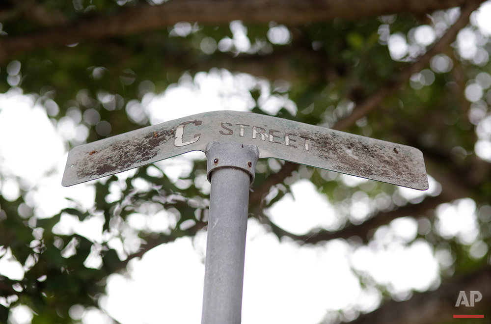 This Tuesday, July 12, 2016 photo shows a bent street sign at the Little Farm trailer park in El Portal, Fla. Residents, many of whom had owned their mobile homes in this close-knit community for years, were evicted in July after the park was purchased in 2015 by Wealthy Delight LLC. The site is now in preliminary planning for mixed use development. (AP Photo/Lynne Sladky) See these photos on  APImages.com