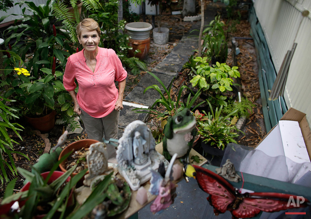 In this Tuesday, July 12, 2016 photo, Nelly Shirley, 74, poses outside of her mobile home at the Little Farm trailer park in El Portal, Fla. She received a Beautification Award for creating the lush, tropical garden around her mobile home where she lived for 22 years, but was evicted in July after the park was purchased in 2015 by Wealthy Delight LLC. She received an $8,000 settlement for her relocation, and is now living in an one-bedroom apartment. The park will be razed. (AP Photo/Lynne Sladky) See these photos on  APImages.com