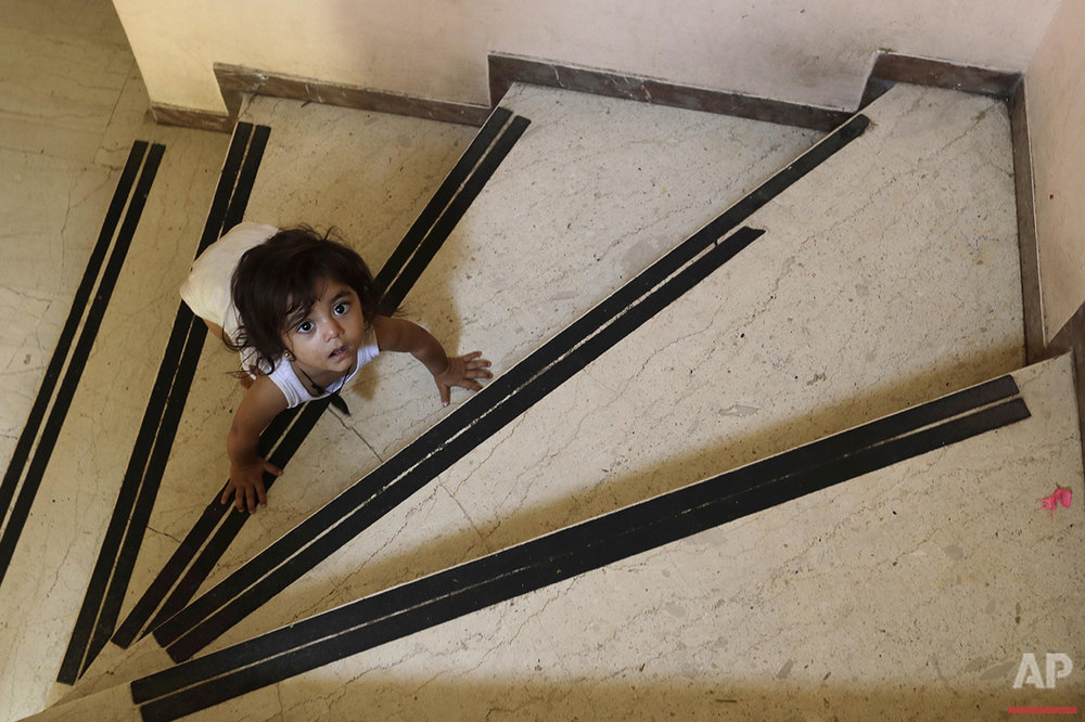 A child crawls on the steps of an abandoned hospital wing, used as a makeshift shelter for around 150 Syrian refugees, in Athens, Wednesday, Aug. 31, 2016. Over 59,000 people remain stranded in the country, most in army-built camps on the mainland and about 7,800 refugees are receiving hotel vouchers or live in vacant apartments. (AP Photo/Thanassis Stavrakis)