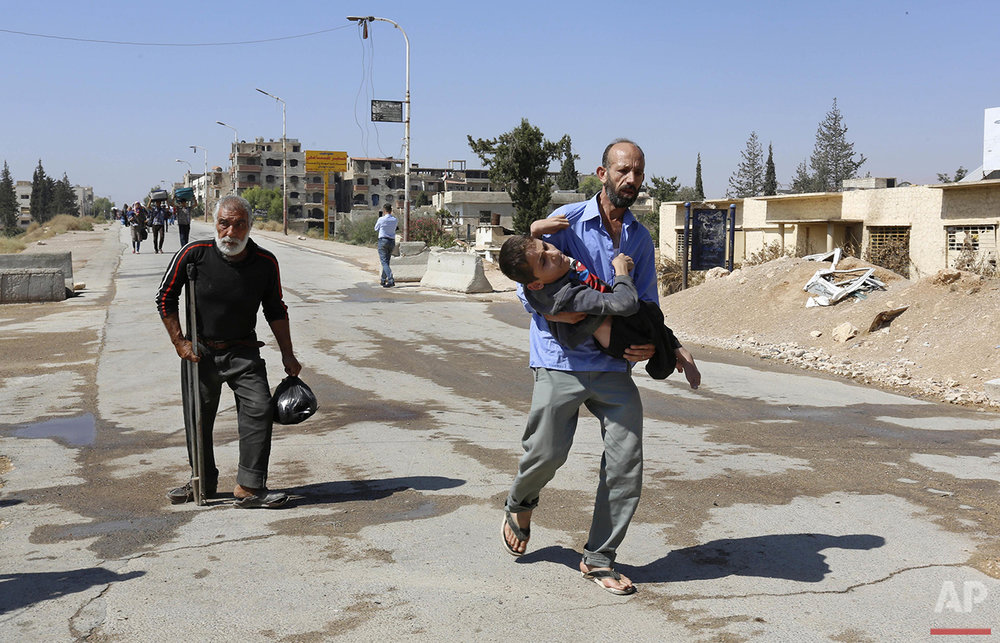 A disabled man is carried as civilians leave the Moadamiyeh suburb of Damascus, Syria, on Friday, Sept. 2, 2016. Dozens of Syrians living in a besieged rebel-held suburb of the capital, Damascus, have begun evacuating the area following a deal struck with the government that grants amnesty to gunmen and restores state control. (AP Photo)