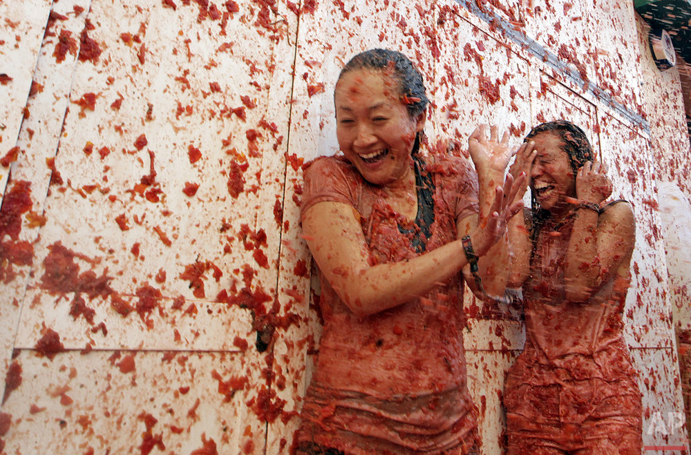 "Revellers throw tomatoes at each other, during the annual ""Tomatina"" tomato fight in the village of Bunol, Spain, on Wednesday, Aug. 31, 2016. At the annual fiesta in Bunol on Wednesday, trucks dumped 160 tons of tomatoes for an estimated 20,000 participants, many from abroad, for the morning festivities. (AP Photo/Alberto Saiz)"