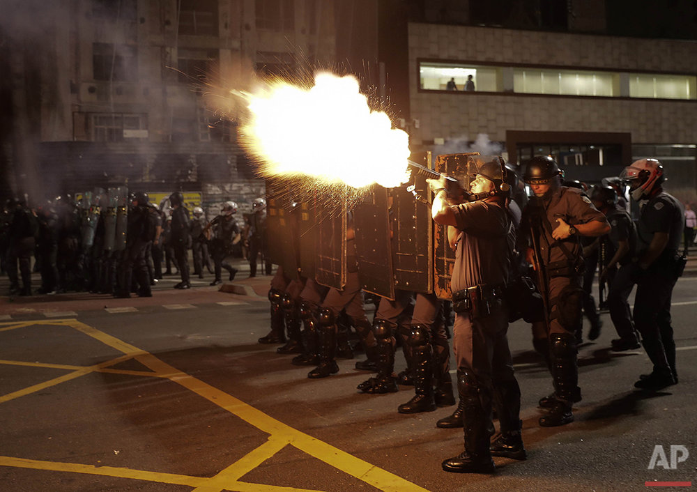 Police fire tear gas against supporters of Brazil's suspended President Dilma Rousseff during a rally in Sao Paulo, Monday, Aug. 29, 2016. On Wednesday, the Senate voted to remove Rousseff for breaking fiscal responsibility laws in her management of the federal budget. Brazil's first female president denies wrongdoing, and has frequently pointed out that previous presidents have used similar accounting measures. (AP Photo/Andre Penner)