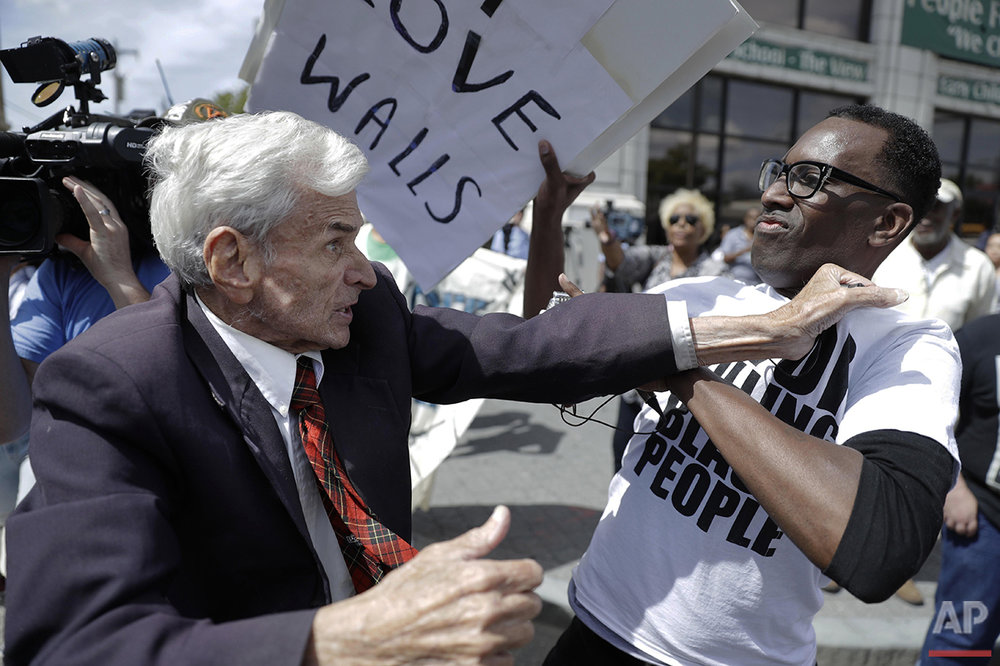 Jerry Lambert, left, a supporter of Republican presidential candidate Donald Trump, and Asa Khalif, a Black Lives Matter supporter, scuffle, after Khalif took Lambert's sign during a protest outside the location where Trump was to meet with African American business and civic leaders in Philadelphia, Friday, Sept. 2, 2016. (AP Photo/Matt Rourke)