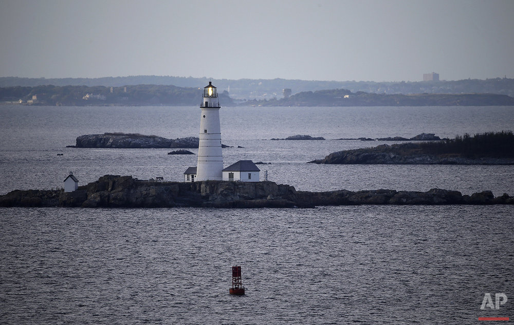 In this Aug. 25, 2016 photo, Boston Light, America's oldest lighthouse, flashes in Boston Harbor as seen from Hull, Mass. (AP Photo/Elise Amendola) See these photos on  APImages.com
