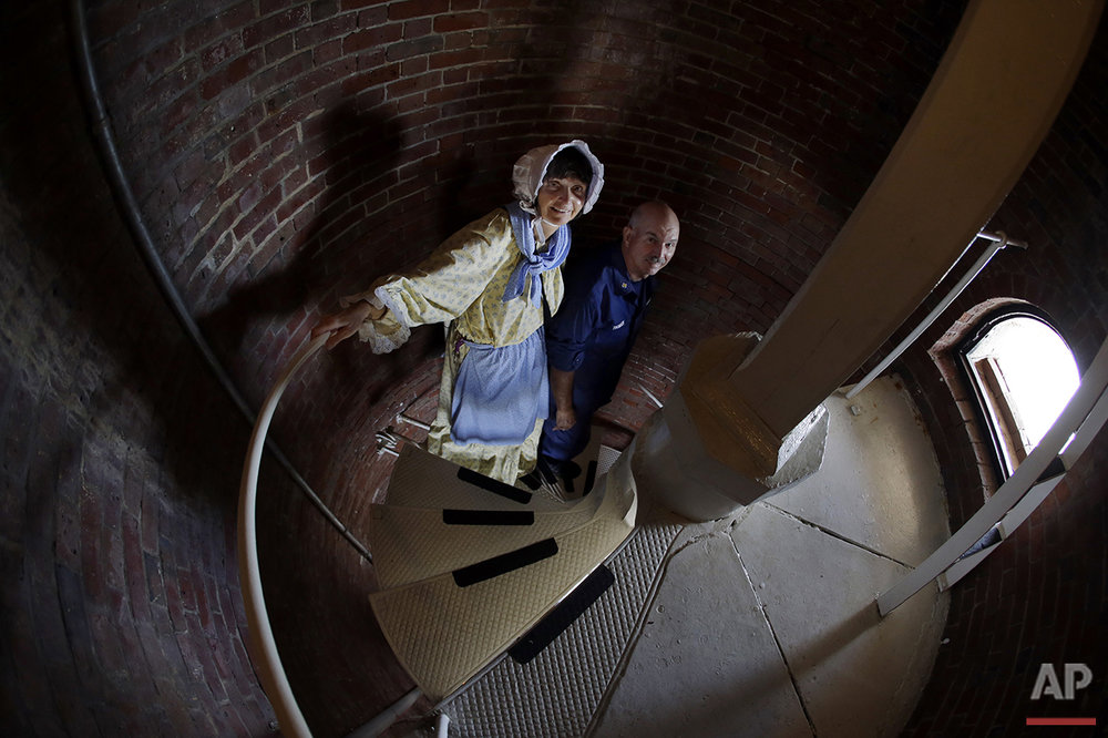 In this Aug. 17, 2016 photo, Sally Snowman, the keeper of Boston Light, and her husband, Jay Thomson of the Auxiliary Coast Guard, climb down the steps inside the lighthouse on Little Brewster Island in Boston Harbor. (AP Photo/Elise Amendola) See these photos on  APImages.com