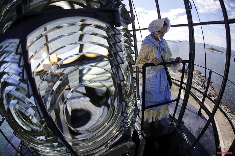In this Aug. 17, 2016 photo, Sally Snowman, the keeper of Boston Light, looks out from the lantern room while standing next to the Fresnel lens, on Little Brewster Island in Boston Harbor. (AP Photo/Elise Amendola) See these photos on  APImages.com