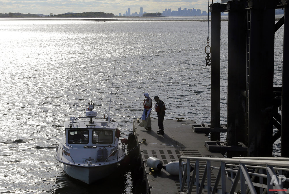 In this Aug. 17, 2016 photo, Sally Snowman, left, the keeper of Boston Light, and her husband, Jay Thomson of the Auxiliary Coast Guard, stand on the dock of Little Brewster Island in Boston Harbor. (AP Photo/Elise Amendola) See these photos on  APImages.com