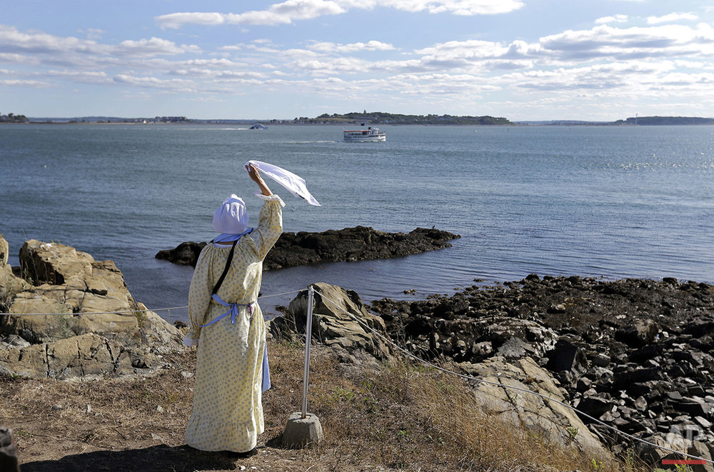 In this Aug. 17, 2016 photo, Sally Snowman, the keeper of Boston Light, waves to a cruise boat from Little Brewster Island in Boston Harbor. (AP Photo/Elise Amendola) See these photos on  APImages.com