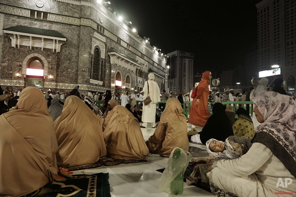 A Muslim woman from Kyrgyzstan, right, sleeps after the Fajr prayer before sunrise, outside the Grand Mosque in the Muslim holy city of Mecca, Saudi Arabia, Thursday, Sept. 8, 2016. Muslim pilgrims have begun arriving at the holiest sites in Islam ahead of the annual hajj pilgrimage in Saudi Arabia, with some weeping with their hands outstretched for a fleeting touch of the Kaaba. The cube-shaped shrine, at the center of Mecca's Grand Mosque, is the site the world's 1.6 billion Muslims pray toward five times a day. (AP Photo/Nariman El-Mofty)