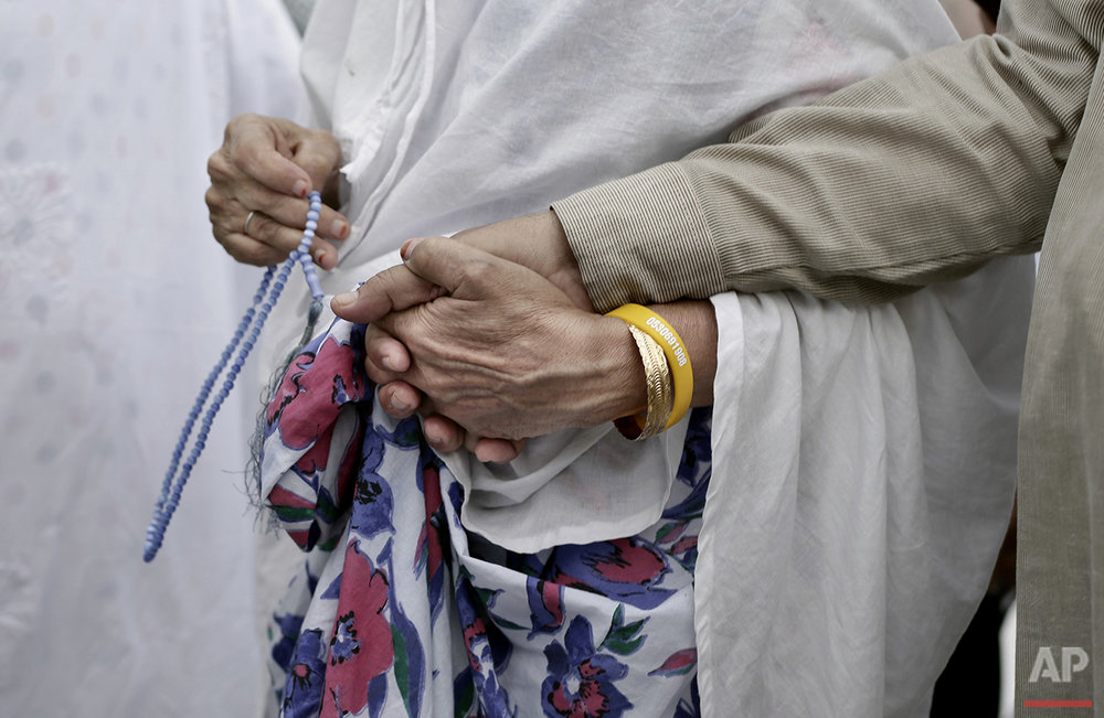An Indian elderly woman leads her husband as they circle the Kaaba, Islam's holiest shrine, at the Grand Mosque in the Muslim holy city of Mecca, Saudi Arabia, Thursday, Sept. 8, 2016. Millions of pilgrims have arrived to Mecca ahead of the Hajj annual pilgrimage which begins Saturday, Sept. 10, 2016. (AP Photo/Nariman El-Mofty)