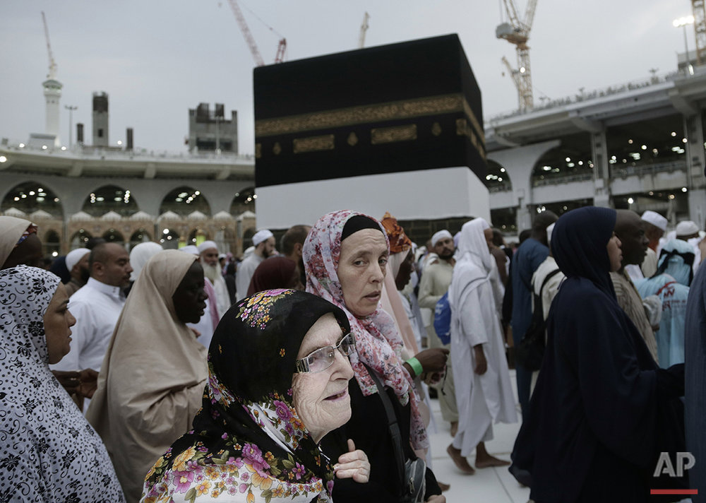 A woman holds her mother as they circle the Kaaba, Islam's holiest shrine, at the Grand Mosque in the Muslim holy city of Mecca, Saudi Arabia, Thursday, Sept. 8, 2016. Millions of pilgrims have arrived to Mecca ahead of the Hajj annual pilgrimage which begins Saturday, Sept. 10, 2016. (AP Photo/Nariman El-Mofty)