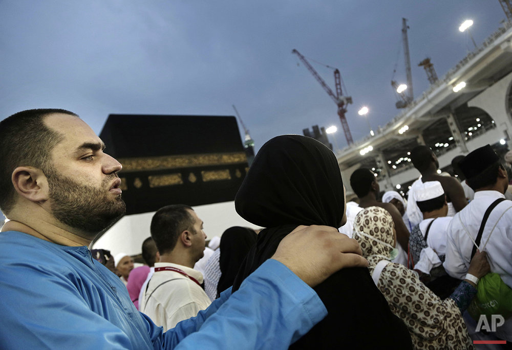 A man holds his wife as they circle the Kaaba, Islam's holiest shrine, at the Grand Mosque in the Muslim holy city of Mecca, Saudi Arabia, Thursday, Sept. 8, 2016. Millions of pilgrims have arrived to Mecca ahead of the Hajj annual pilgrimage which begins Saturday, Sept. 10, 2016. (AP Photo/Nariman El-Mofty)