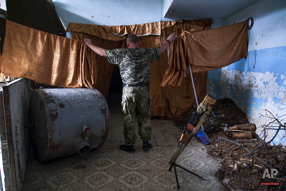 In this photo taken on Thursday, Aug. 25, 2016, a Ukrainian soldier walks along a corridor damaged by shelling in the village of Marinka, near Donetsk, eastern Ukraine. More than 9,500 people have been killed in the fighting that began in April 2014, according to United Nations figures, but despite the carnage or the weariness of those inflicting it, there's little expectation it will actually stop anytime soon. (AP Photo/Max Black) See these photos on  APImages.com