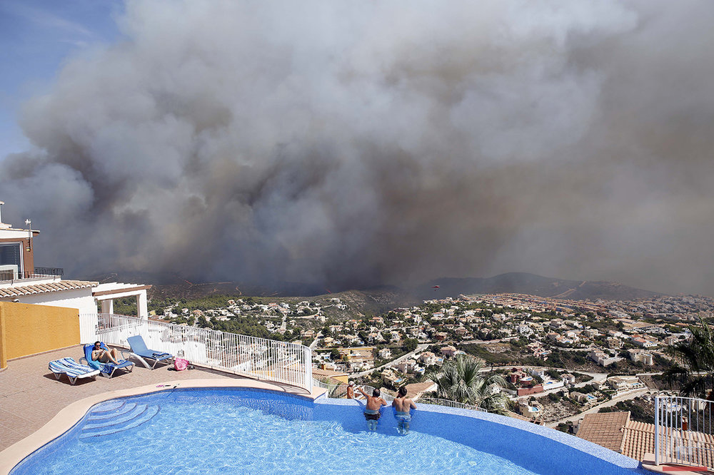 Two men look at a wildfire from a swimming pool as it burns nearby Benitachel village, eastern Spain, Monday, Sept. 5, 2016. (AP Photo/Alberto Saiz)