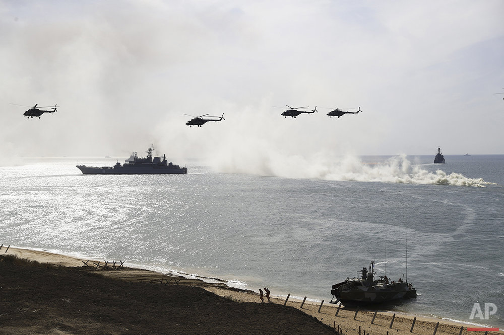 Russian navy ships and helicopters take part in a landing operation during military drills at the Black Sea coast, Crimea, Friday, Sept. 9, 2016. Russia has deployed cruise missiles, multiple rocket launchers, tanks and its latest anti-aircraft system at massive military drills on the peninsula. The drills, involving over 120,000 troops, are some of the largest exercises Russia has held for years. (AP Photo/Pavel Golovkin)