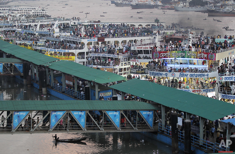 A boy rows a boat, bottom left, past a ferry terminal crowded with people traveling to their hometowns for Eid al-Adha festival in Dhaka, Bangladesh, Friday, Sept. 9, 2016. Muslims around the world celebrate Eid al-Adha, the Feast of the Sacrifice, to commemorate the prophet Ibrahim's faith for his willingness to sacrifice his son. (AP Photo/A.M. Ahad)