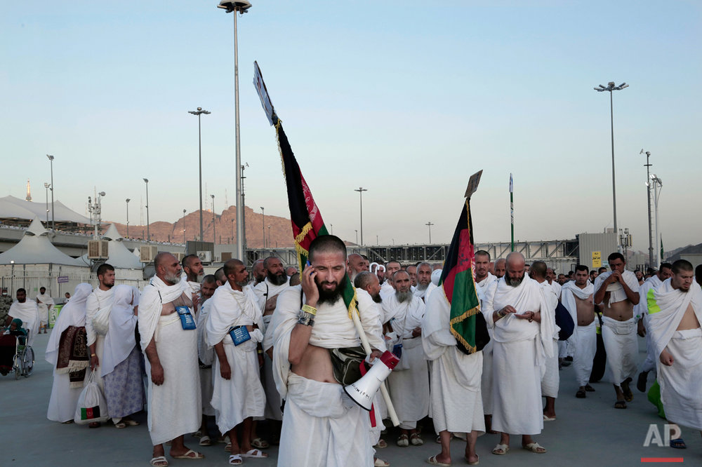 "Afghan Muslim pilgrims make their way to cast stones at a pillar symbolizing the stoning of Satan, in a ritual called ""Jamarat,"" the last rite of the annual hajj, on the first day of Eid al-Adha, in Mina near the holy city of Mecca, Saudi Arabia, Monday, Sept. 12, 2016. (AP Photo/Nariman El-Mofty)"