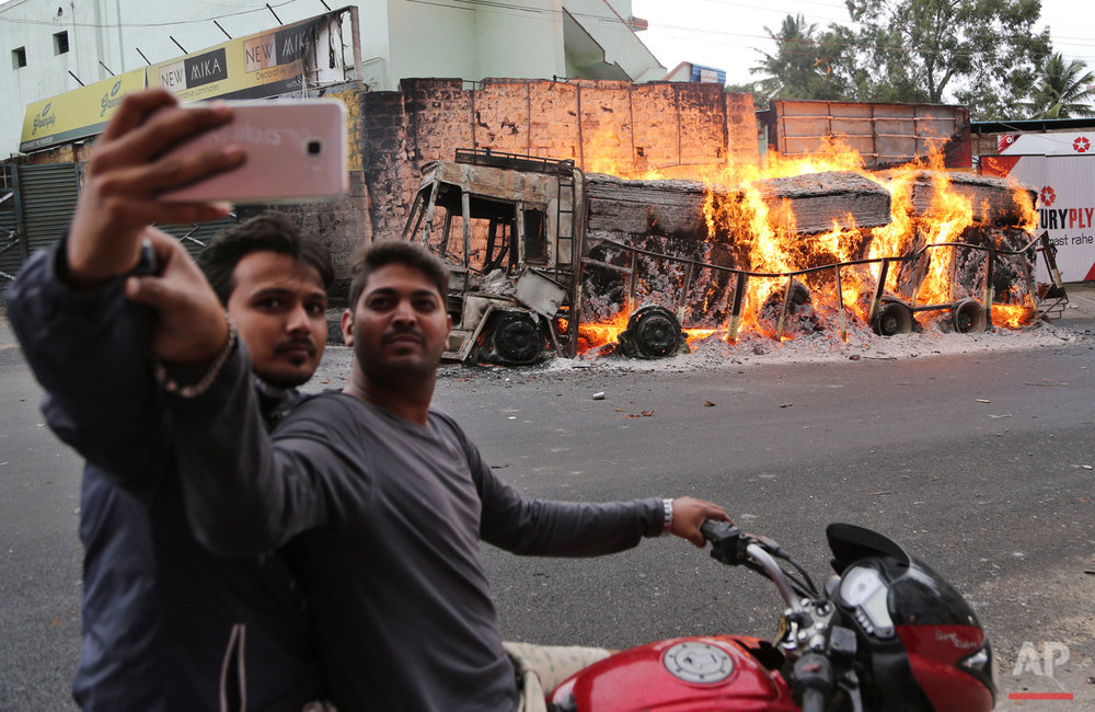 Two men on a motorcycle stop to take a selfie with a burning truck from neighboring Tamil Nadu state, after it was set ablaze by angry mobs in Bangalore, Karnataka state, India, Monday, Sept. 12, 2016. India's top court on Monday ordered the southern state of Karnataka to release water from a disputed river to neighboring Tamil Nadu after violence erupted in both states over water sharing. (AP Photo/Aijaz Rahi)