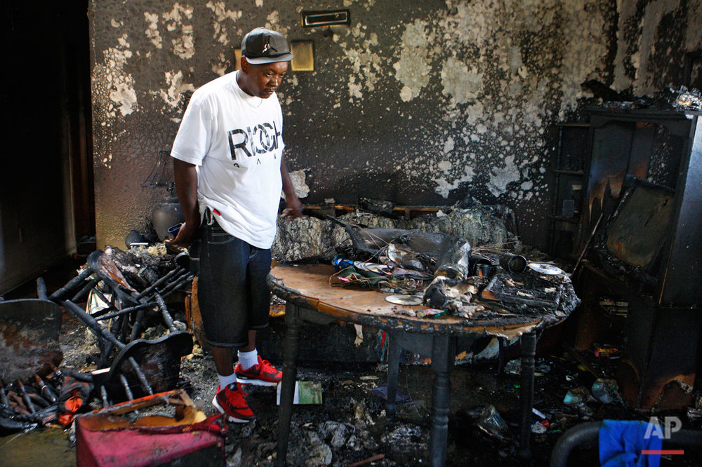 Frederick Terrell looks inside the home where an early morning fire killed multiple people, including children, Monday, Sept. 12, 2016, in Memphis, Tenn. Terrell said he is a friend of the family that lived in the home. (AP Photo/Karen Pulfer Focht)
